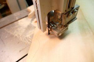 Uitzagen met de lintzaag machine van het bovenblad van de cello